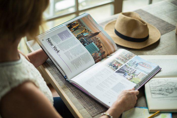 Девушка за столиком читает книгу, которая открыта на странице о Нью-Йорке