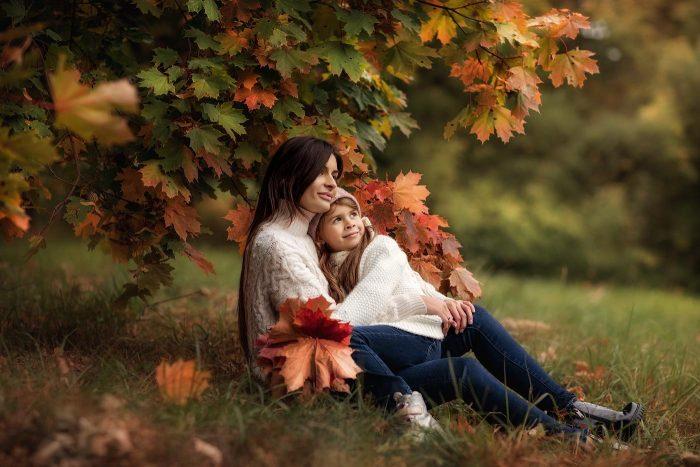 Мама с дочкой сидят под деревом с разноцветными осенними листьями