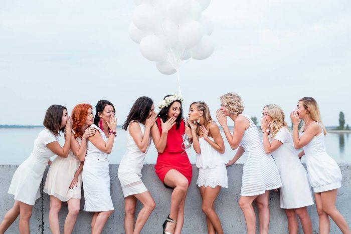 Восемь девушек в белых платьях и одна в красном позируют у парапета