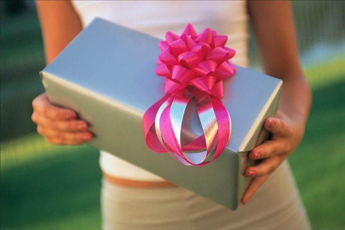 Девушка держит подарочную коробку с украшением в виде красного цветка