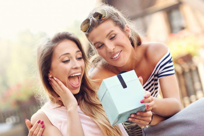 Девушка в восторге смотрит на коробочку, что подарила подруга