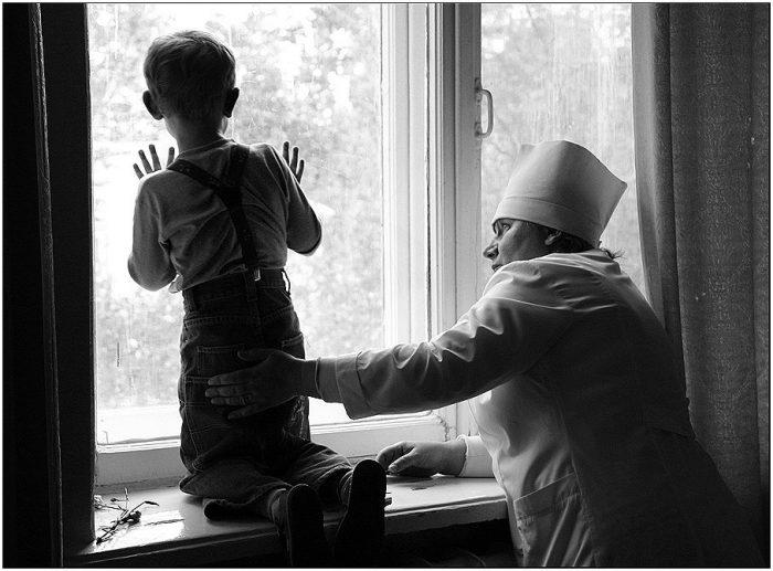 мальчик с медсестрой смотрят в окно