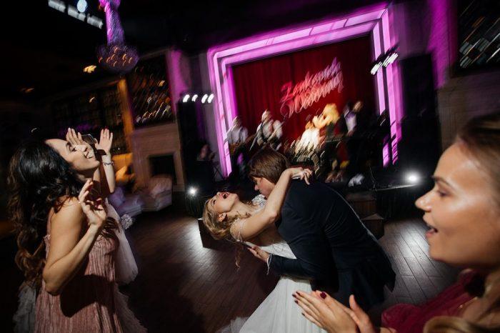 невеста и жених танцуют на фоне сцены с группой
