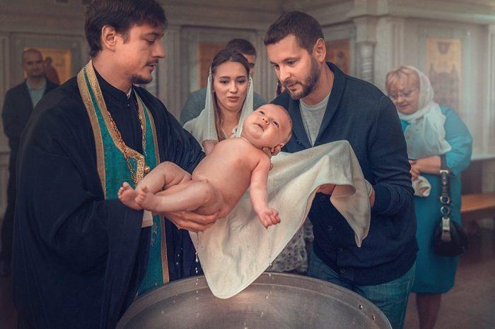 Младенца вынимают из купели во время крещения