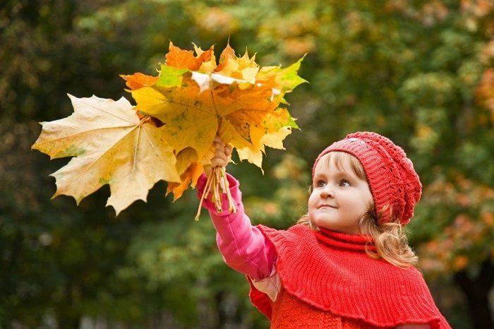 У девочки в руке букет из осенних листьев