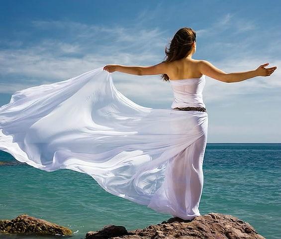 Девушка в прозрачном белом платье со шлейфом стоит на берегу моря, раскинув руки