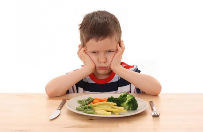 Мальчик с недовольным видом сидит за столом, перед ним тарелка с овощами