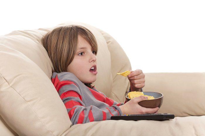 Ребёнок перед телевизором с тарелкой чипсов