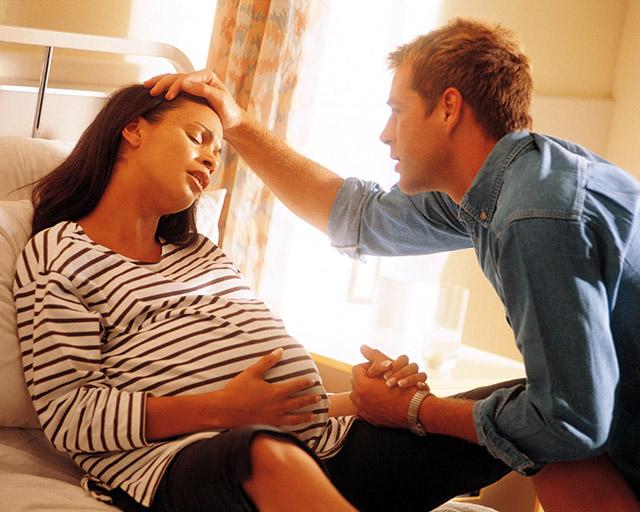 Беременная лежит на кровати и держится за живот, её держит за руку муж