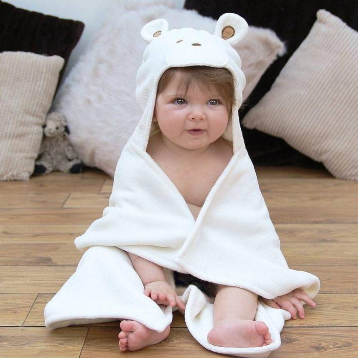 Ребёнок в полотенце сидит на полу