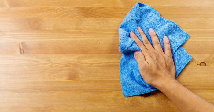 Женщина протирает поверхность кухонным полотенцем