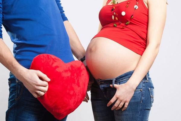 Мужчина и беременная женщина, в руках мужчины плюшевое сердце