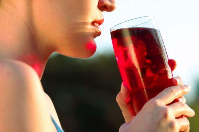 Женщина пьёт клюквенный морс
