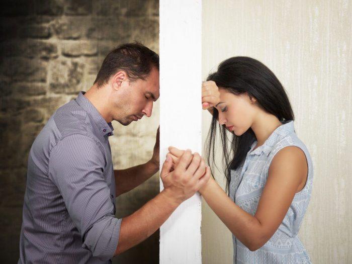 Мужчина и женщина держатся за руки через стену между ними
