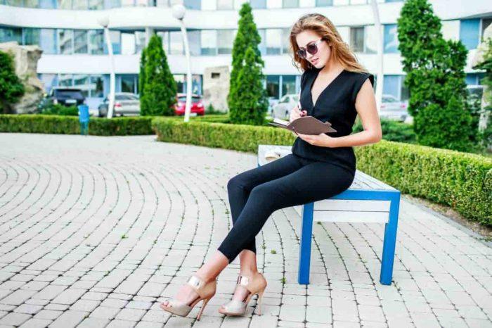 Девушка читает на скамейке в парке