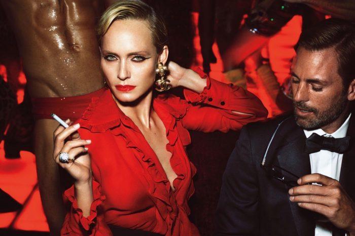 Женщина с сигаретой в красном костюме, и мужчина рядом смотрит ей в декольте