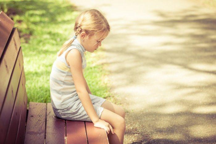 Грустная девочка сидит на лавке